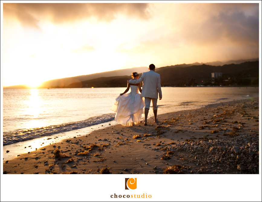 Bride and Groom walking at sunset on the beach