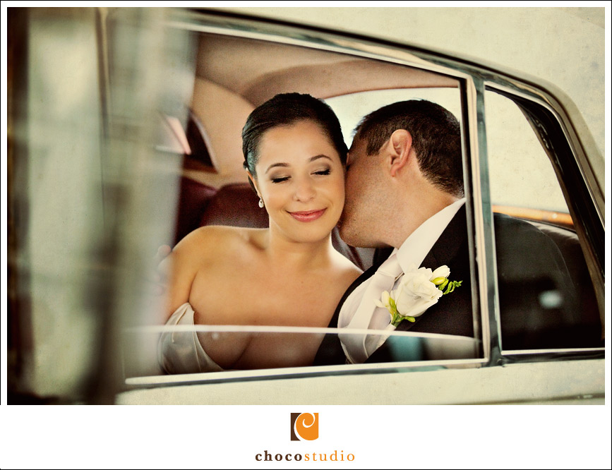 Bride and groom kissing inside the vintage classic car