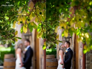 Bride and groom kissing portrait under plum tree in front of Mankas Gardens barrel room at Vezer winery wedding