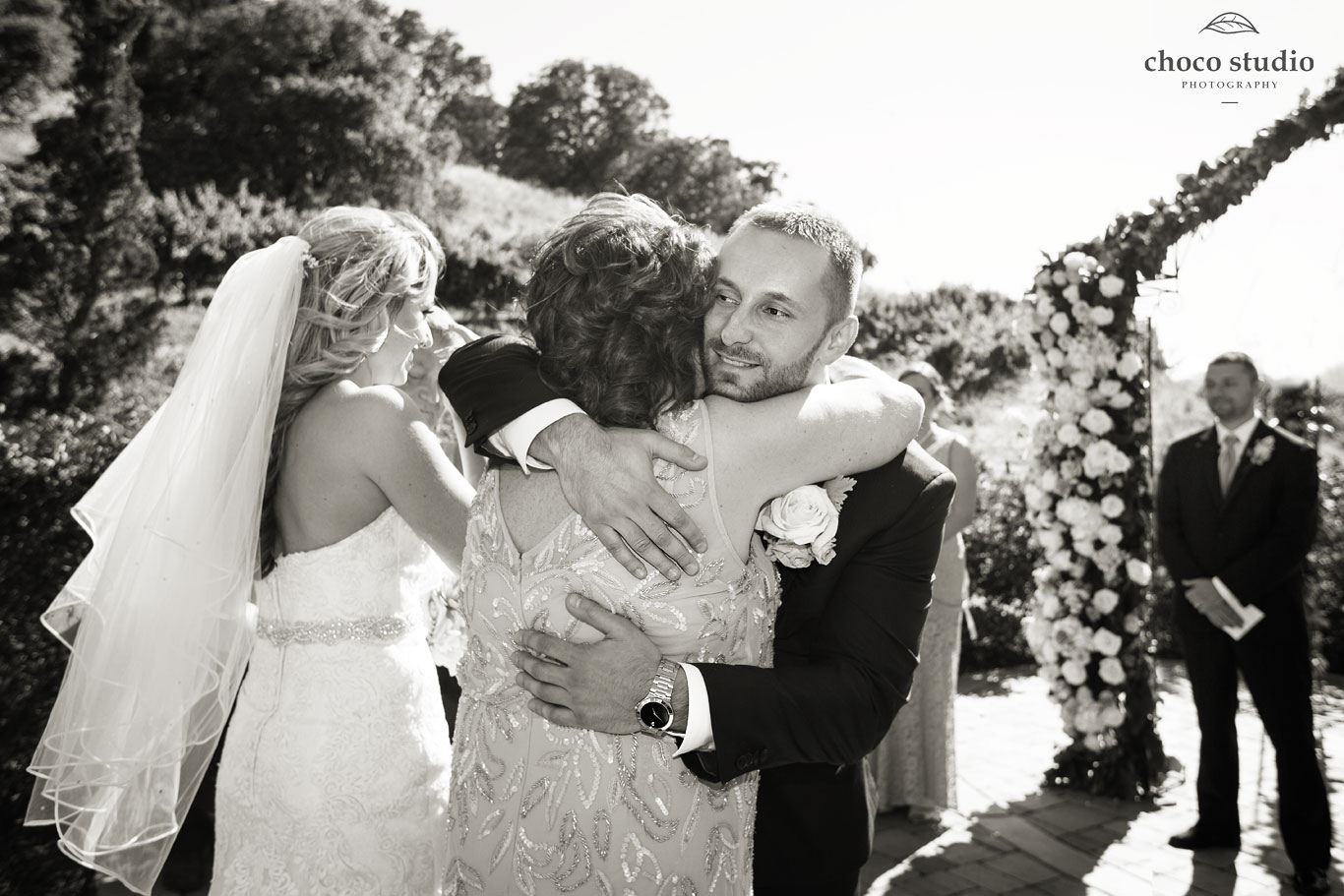 Groom hugs parent during wedding ceremony at Ranch Estate Vineyard Lookout at Vezer winery wedding