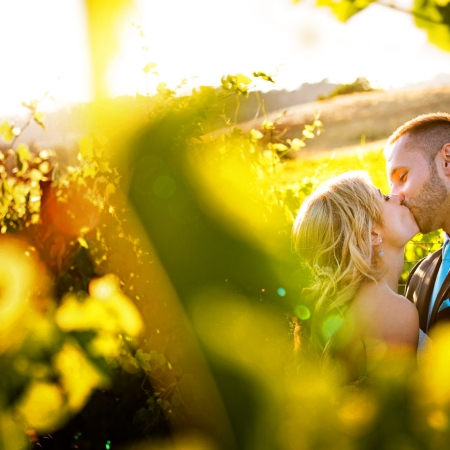 Bride and groom kissing during sunset vineyard portrait at Ranch Estate Vineyard Lookout and Courtyard at Vezer winery wedding
